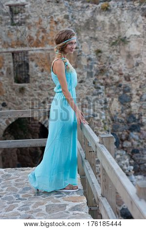 Young blonde woman in  turqoise maxi dress with braided hair against blurred stone castle wall