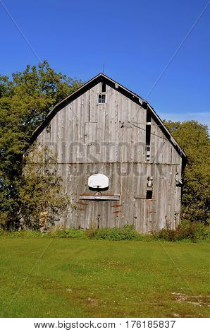 A huge hip roofed weathered old barn with a basketball hoop and rim.