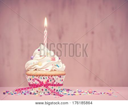 Birthday Cupcake with candle and sprinkles over a pink background. Antique tone effect added.
