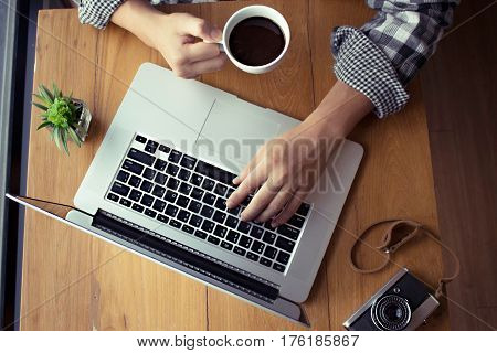 young man working on his laptop in a coffee shop rear view of business man hands busy using laptop at office desk Workspace with laptop notebook . Flat lay top view office table desk.