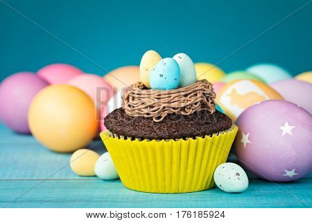 Colorful Easter Eggs and cupcake with nest on a blue background.