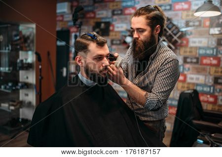 Barber cutting hair of client man in salon cape
