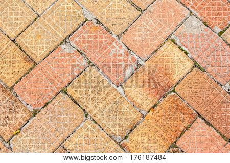 Section of an old brick sidewalk with a nice pattern and varying shades of browns and reds