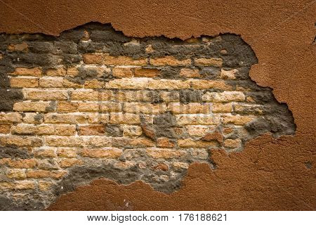 Cracked concrete wall with an exposed brick background.