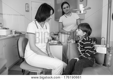 Child with doctor and assistance look at the camera
