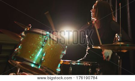 Gothic black hair girl percussion drummer perform music break down - teen rock music, telephoto