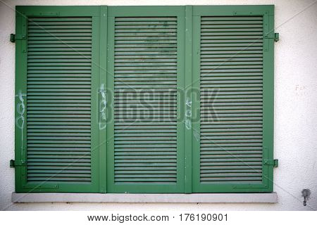 Green colored shutters on a nostalgic window.