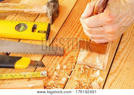 Senior woodworker or carpenter doing woodworking on a plank of wood in workshop with manual plane