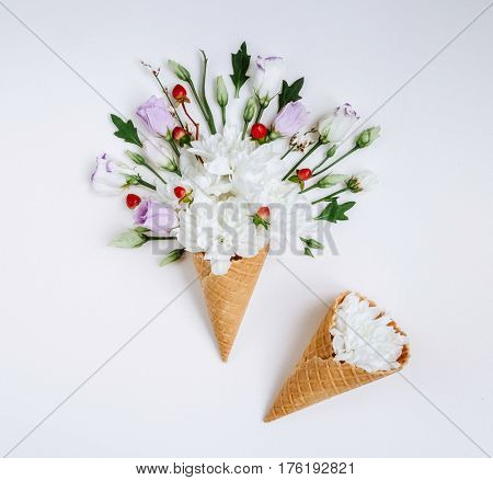 Lovely leaves flower in ice cream cone on white background. Floral arrangement, flat lay styling. Top view. Creative still life idea of spring wallpaper. Picturesque and gorgeous scene. Beauty world.