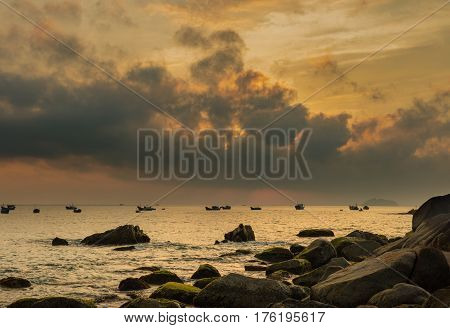 A fiery orange morning sky looking out over the south China sea in Vung Lam Bay Vietnam. With a rock covered coastline and fishing boat silhouettes.