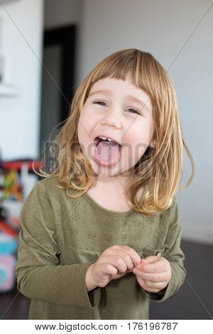funny portrait of three years old child face with green shirt and touching her finger looking laughing and sticking her tongue out