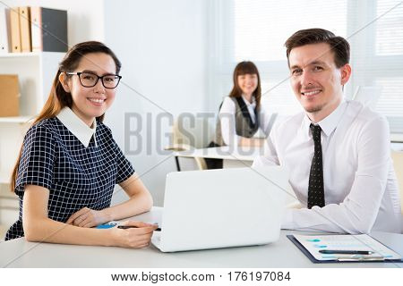 Young businesspeople working with laptop in office