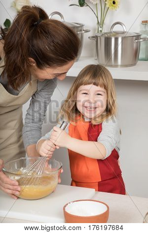 happy woman mother with glass bowl and three years old child looking smiling and whipping with whisk in teamwork making and cooking a sponge cake at kitchen home