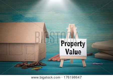 Property Value. home model, money and a notice board under the sunlit.