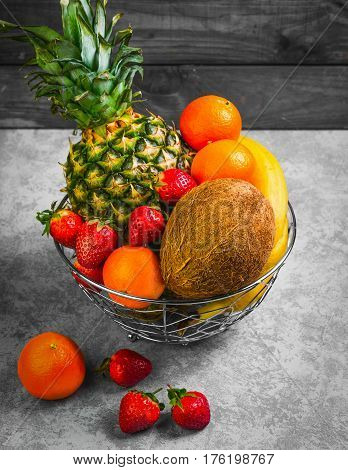 Exotic tropical fruit pineapple coconut berries strawberries mandarins clementines bananas in metal bowl basket of fruit on gray background.
