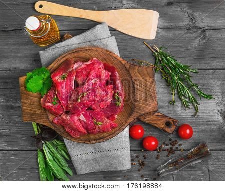Fresh raw chopped meat beef on an wooden board plate. Raw ingredients spices herbs thyme coriander basil olive oil and vegetables on gray wooden background for raw chopped meat beef. Top view