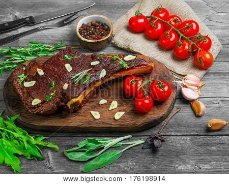 T-bone steak cow meat rib eye grilled on the board. Ingredients for T-bone steak cow meat rib eye grilled Tomatoes rosemary sage leaves thyme basil arugula garlic pepper. Gray wooden rustic background.
