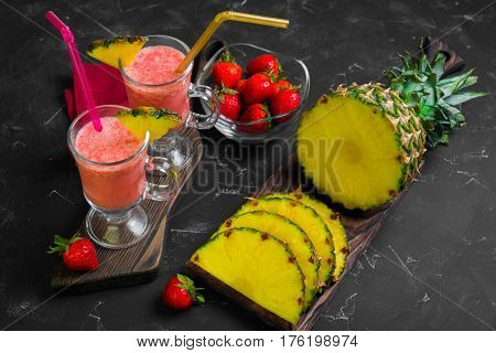 Summer Fruit cocktail smoothie with strawberries and pineapple in the glasses. Ingredients for cocktail smoothie of fresh strawberries and pineapple. Dark black background.