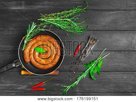 Grilled sausage snail coil spiral on the Fry pan barbecue. Ingredients for Grilled sausage snail Thyme rosemary arugula pepper. Dark black wooden background. Top view from above and copy space.