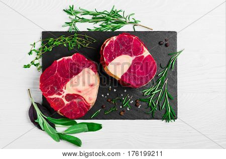 meat beef veal shank slices meat for Osso Buco cooking on white wooden background. Ingredients for beef meat Osso Buco sage leaves thyme rosemary pepper salt pepperl. Top view.