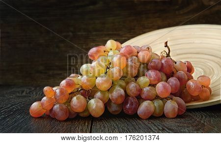 the grapes are ripe bunch of grapes lying on a round wooden plate on dark background