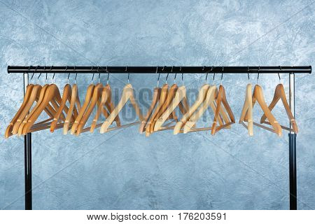 Clothes rail with wooden hangers on color background