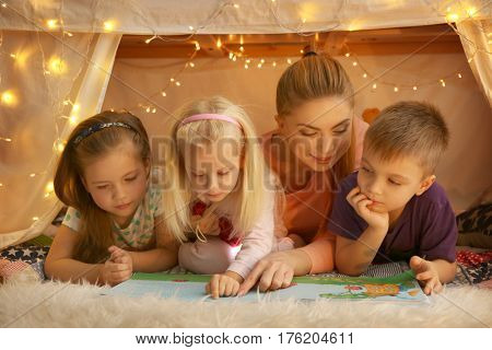 Young woman and cute children reading book in hovel at home