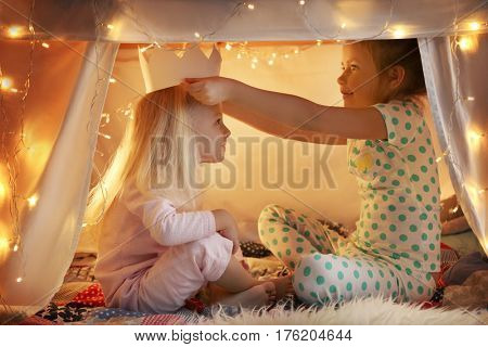 Cute little girls playing in hovel at home