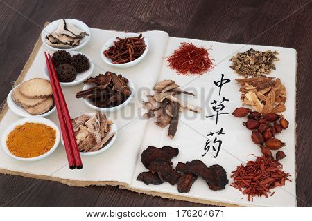 Chinese herb selection used in herbal medicine with chopsticks on a hemp notebook with calligraphy script on rice paper translated as chinese herbs.