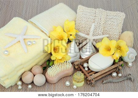 Natural spa beauty cleansing products with freesia flowers, shells and pearls on bamboo background.