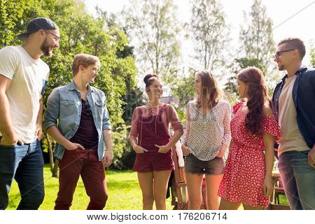 leisure, holidays, reunion, people and friendship concept - happy teenage friends talking at summer garden