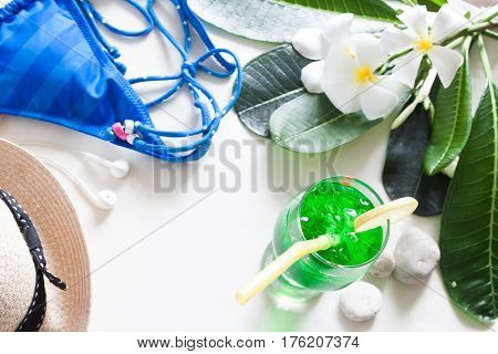 Summer concept iced green color drink blue stripe bikini and plumeria flower on white background with copy space