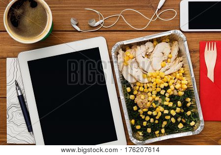 Healthy business lunch at workplace. Top view flat lay of desktop - tablet pc with copy space and phone on wooden desk background with snack in foil container