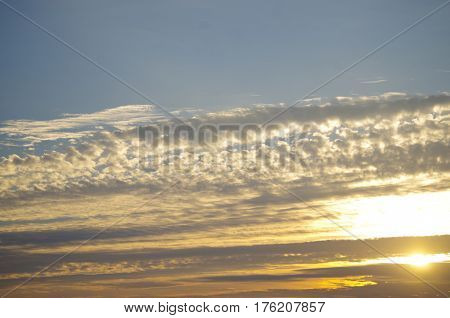 Sun peaking through streaks of dark and amber morning cloud separated from a blue sky by a long white fishbone cloud.