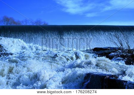 Dam with flowing water. Blue sky on background.