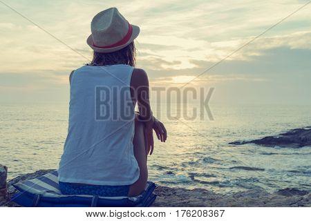Lonesome girl watching the sunset / sunrise over sea / ocean horizon.