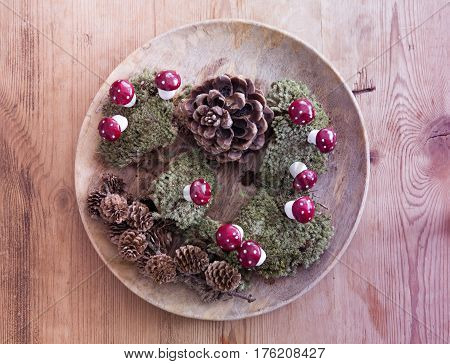 wooden bowl with pinecones and moss and mushrooms on wooden table