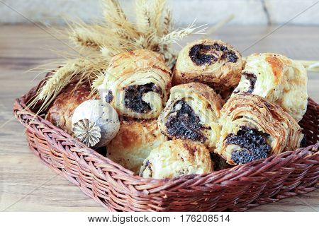 Sweet buns with poppy seeds lie in a wicker basket, on a wooden table and near a stone wall - sandstone. Poppy head and spikelets lie on sweet rolls