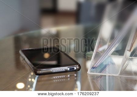 Background blur Photo focus select at mobile phone and brochure in acrylic box on table Blur background decor showroom customer service area has copy space.