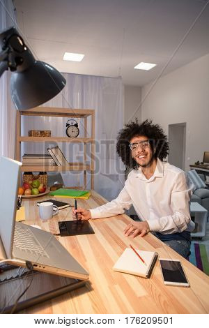 Happy hipster freelance man working at table and smiling for camera. Handsome man in glasses sitting at table and using editing board at home. Freelance concept.
