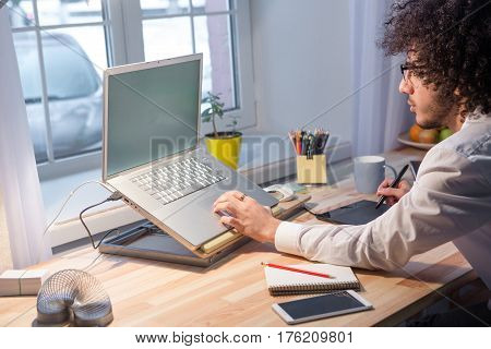 Side view of hipster freelance man using laptop computer while sitting at table and working at home alone. Business or freelance concept.