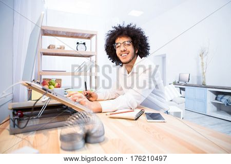 Happy smiling hipster freelance man working at table with laptop computer. Handsome man in glasses looking at camera at home. Business or freelance concept.