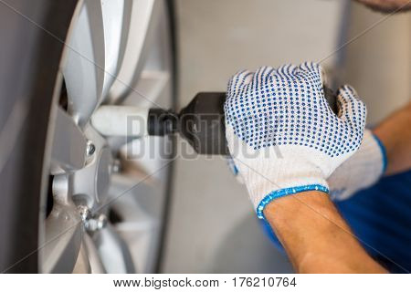 car service, repair, maintenance and people concept - auto mechanic man with cordless screwdriver changing tire at workshop