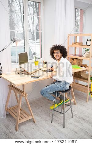 Business or freelance concept. Hipster freelance man working on laptop computer and looking at camera at home. Handsome man working as web designer.