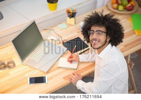Top view of happy hipster freelance man looking at camera while working at table in front of laptop computer at home alone. Freelance or business concept.