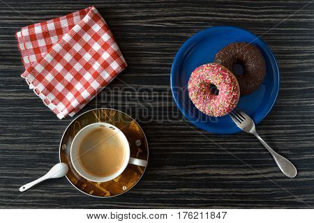 Morning hot coffee, two donuts on a blue plate one pink another chocolate. Red checkered napkin. Black background