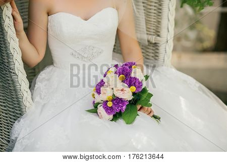 Bride holding delicate and tender marriage bouquet in purple and pink colours with green petals