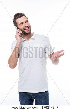 Excited young man talking on smartphone and gesticulating on white