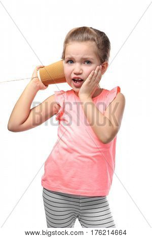 Cute little girl using plastic cup as telephone, on white background