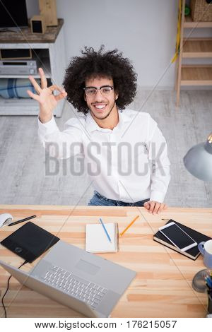 Freelance or business concept. Hipster freelance man in glasses showing yo or okay sign to camera while sitting at table and working on laptop computer at home.